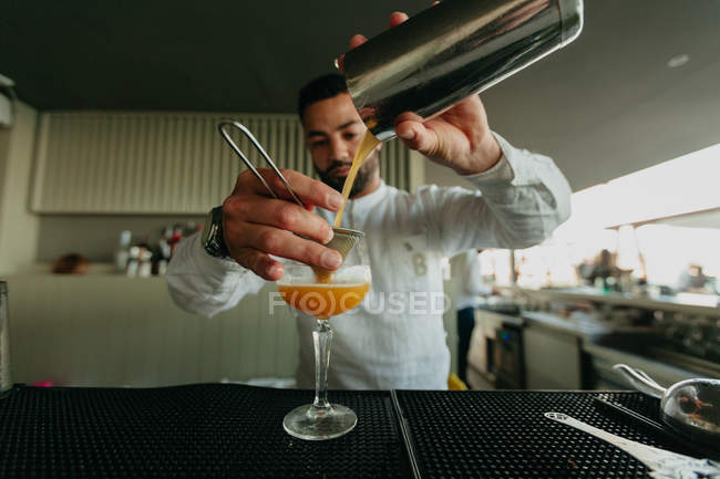 Bartender pouring cocktail from shaker in glass in bar — Stock Photo