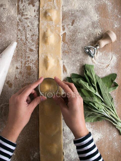 Купка стиглої скорботи і різні начиння покласти на борошно біля неприготованих равісів і тісто на кухонному столі. — стокове фото