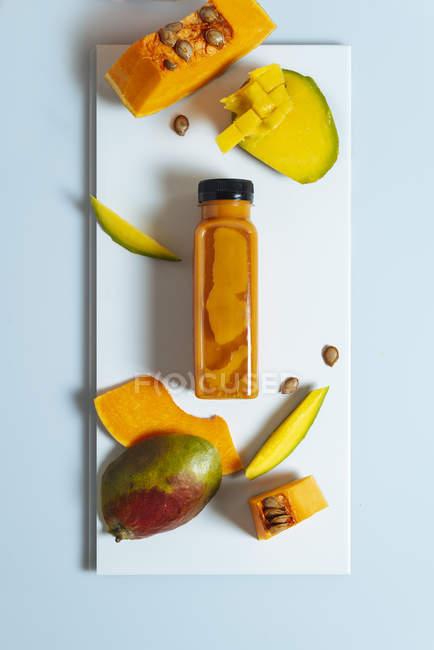 Batido vegano de mango y calabaza en botella sobre pizarra blanca con ingredientes - foto de stock