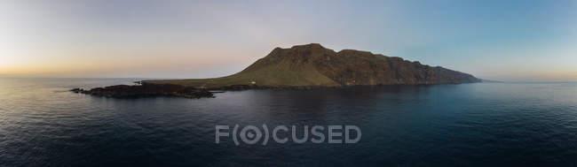 Vue panoramique sur le littoral avec des falaises majestueuses et des vagues sombres au coucher du soleil — Photo de stock