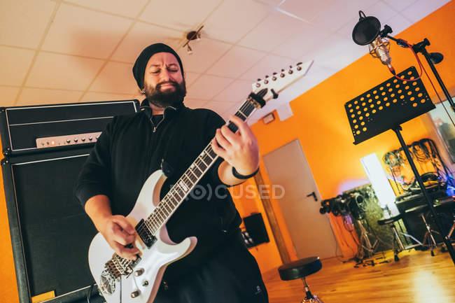 Erwachsener Mann im Musikstudio spielt Gitarre — Stockfoto