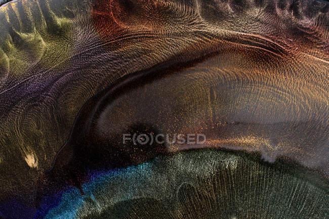 Spills of multicolored metallic dye mixing together — стокове фото