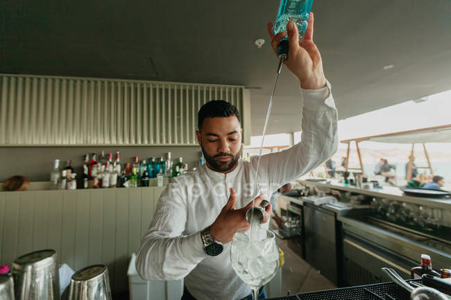 Bartender pouring alcoholic drink in glass in bar — Stock Photo