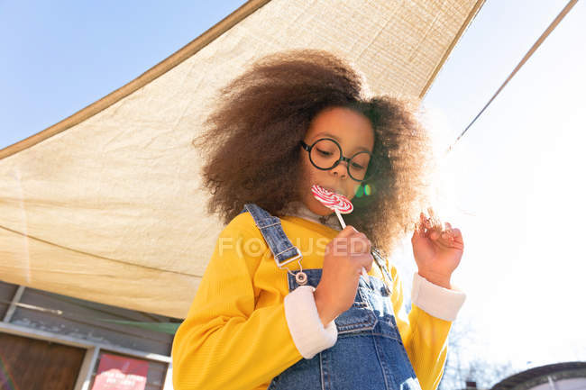 Portrait of African American girl eating big lollipop — Stock Photo