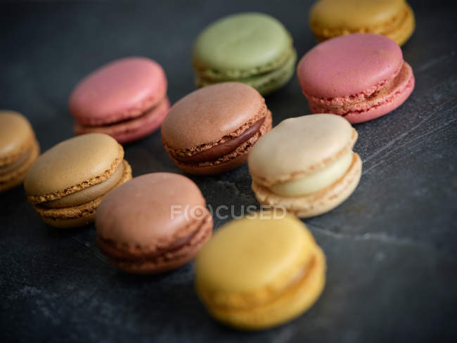 Bright fresh tasty macarons scattered on grey background — Stock Photo