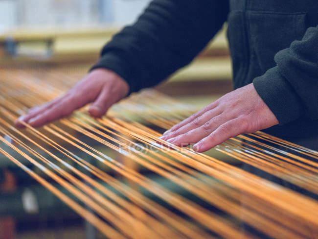 Руки працівника торкаючись помаранчевої бавовняної нитки на Ткацький верстат на заводі — стокове фото