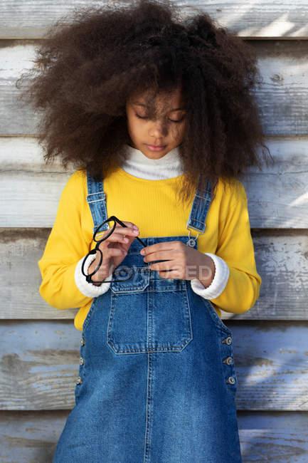 Simpatica ragazza afroamericana in tuta di jeans in piedi contro muro di legno — Foto stock