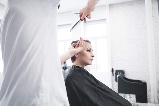 Волосся жінки підстригає ножицями. — стокове фото