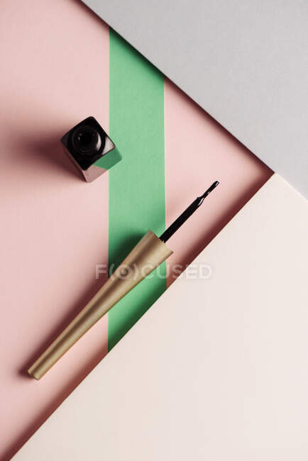 Pennello eyeliner liquido, su sfondo attraente, di colori rosa pastello e verde. Concetto di prodotto e trucco. Dall'alto — Foto stock