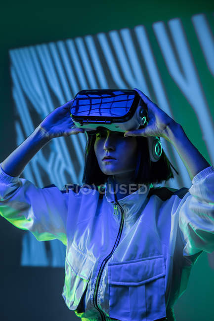 Excited young woman wearing virtual reality goggles in neon light — Stock Photo