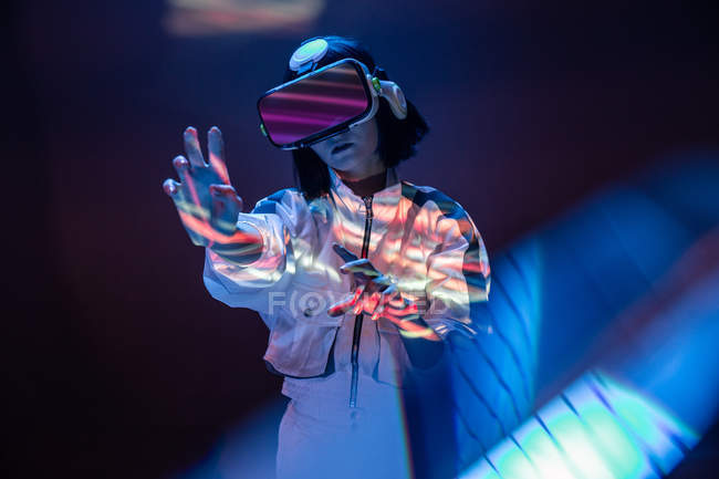 Excited young woman touching air while having virtual reality experience in neon light — Stock Photo