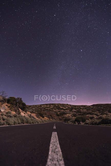 Camino vacío por la noche bajo estrellas brillantes - foto de stock
