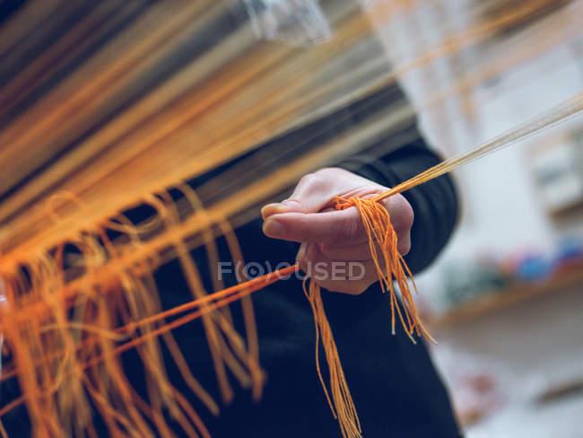 Рука человека, держащего нити на ткацком станке — стоковое фото