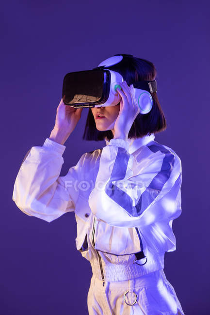 Excited young woman having virtual reality experience in neon light — стокове фото