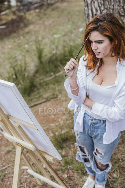 Young woman painting in countryside — стокове фото
