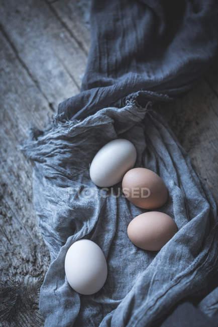 Hühnereier auf Tischdecke auf rustikalem Holztisch — Stockfoto