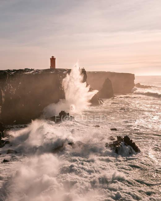 Ondas da tempestade na costa ocidental de Islândia e do farol de Svrtuloft na distância — Fotografia de Stock