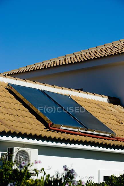 Загородный коттедж с солнечными батареями, установленными на черепичную крышу на фоне безоблачного голубого неба — стоковое фото