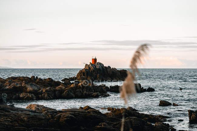 Piccolo faro rosso situato sulla costa rocciosa vicino al mare increspato contro il cielo serale nel Monte Maunganui, Nuova Zelanda — Foto stock