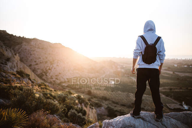 Back view of male hiker in sportswear standing on rocky cliff above terrain looking at picturesque landscape in morning sunlight — Stock Photo