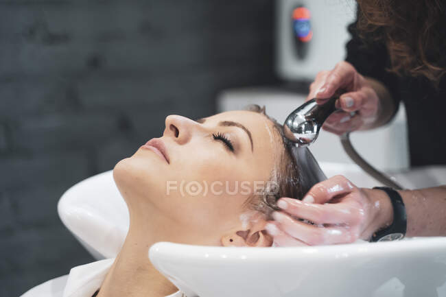 Stylist washing hairs to young lady — Stock Photo