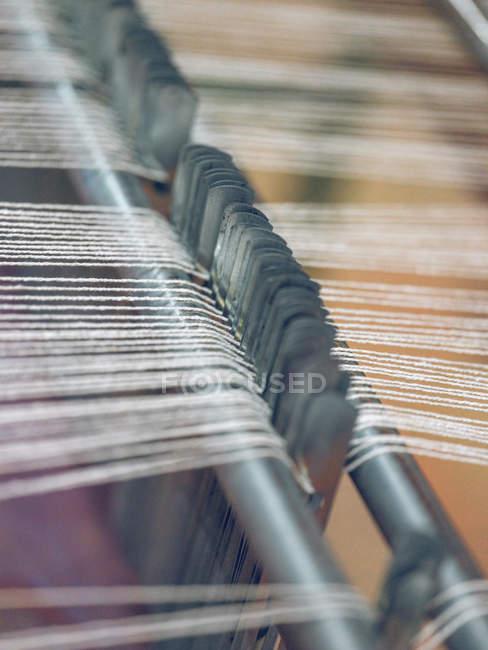 Close-up das linhas brancas no tear na fábrica — Fotografia de Stock