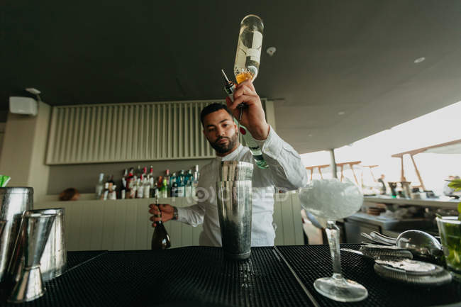 Barman pouring alcoholic drink to shaker in bar — Stock Photo