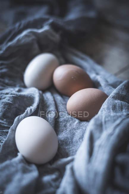 Huevos de pollo en mantel sobre mesa de madera rústica - foto de stock