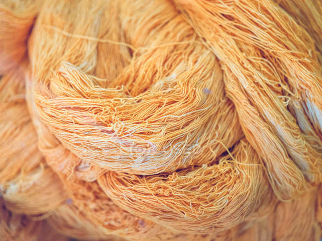 Pile of dirty and wavy cotton thread of orange color on factory — Stock Photo