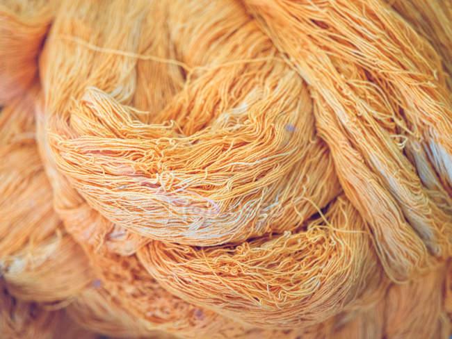 Haufen von schmutzigen und welligen Baumwollfaden von orange Farbe auf Fabrik — Stockfoto
