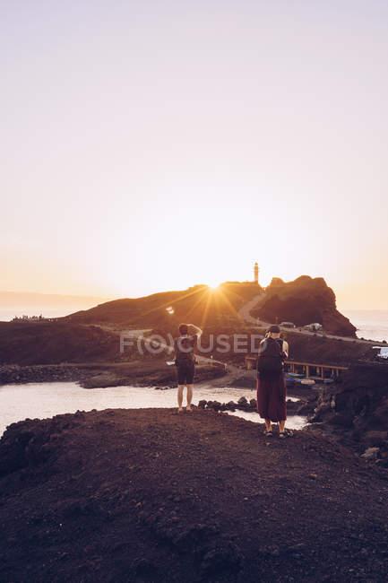 Чоловік, мандрівники приймають фото на березі моря на заході сонця — стокове фото