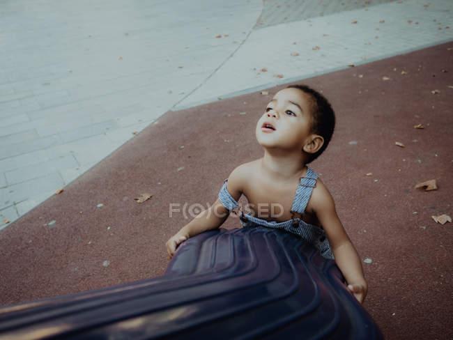 Adorable enfant jouant dans une aire de jeux en plein air — Photo de stock