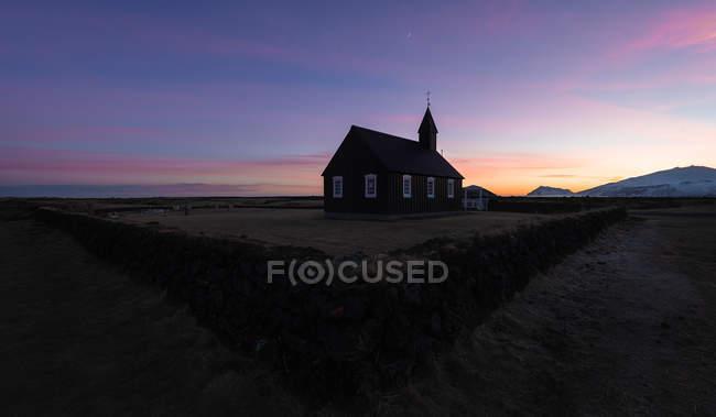 Горный пейзаж с черной деревянной христианской церковью Budakirkja в Исландии — стоковое фото