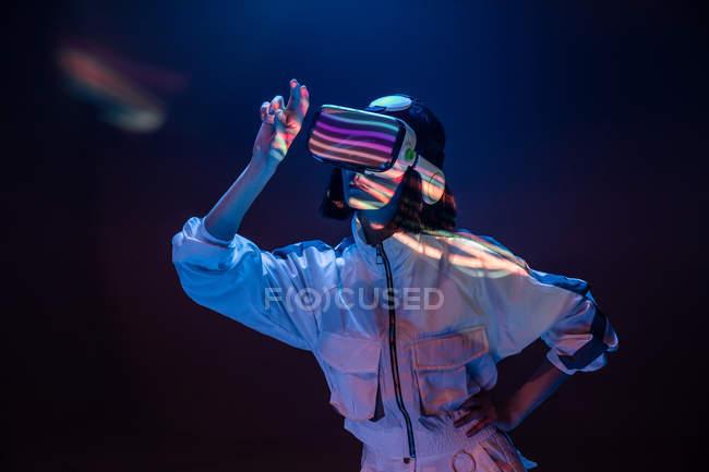 Mujer joven emocionada tocando el aire mientras tiene experiencia de realidad virtual en luz de neón - foto de stock