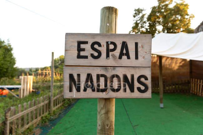 Segno di legno squallida con scritta sulla lingua catalana collocata in una zona chiusa in campagna — Foto stock