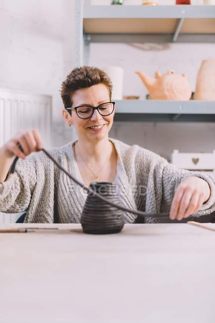 Adult female potter putting soft clay strip on top of vase while sitting at table in workshop — стокове фото
