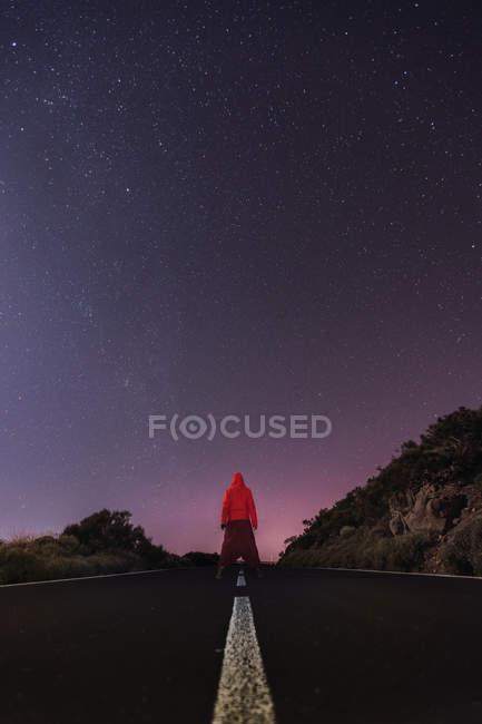 Viajante com capuz vermelho jaqueta de pé na estrada vazia à noite — Fotografia de Stock