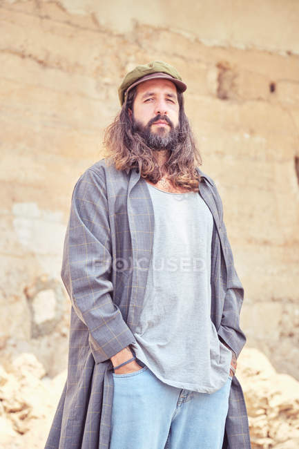 Stylish bearded man with long hair on street posing and looking at camera — Stock Photo
