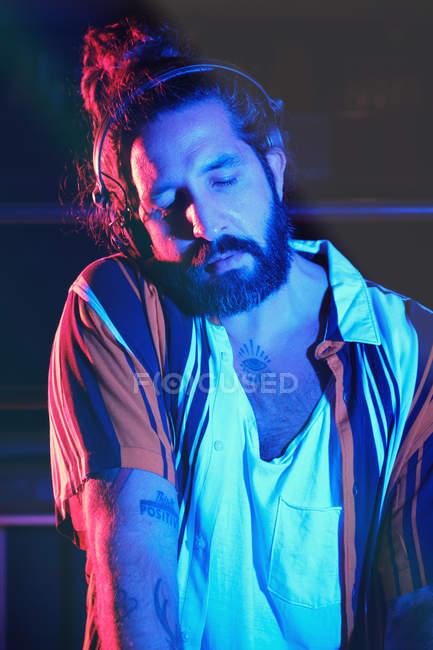 Barbudo dj hombre jugando disco música en un club - foto de stock