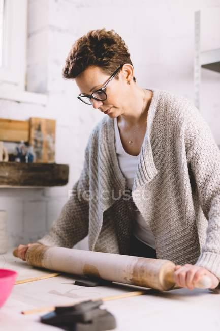 Alfarero hembra adulta usando rodillo en pieza de arcilla suave mientras trabaja en taller profesional - foto de stock