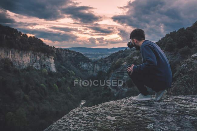 Homme avec appareil photo assis sur la montagne de colline avec magnifique coucher de soleil — Photo de stock