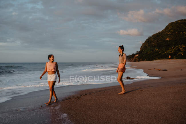 Two slim young females in shorts and bras smiling and looking at each other while standing on sandy shore against cloudy gray sky — Stock Photo
