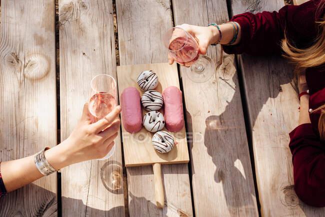 Mani di donne con occhiali da vino al tavolo da picnic — Foto stock