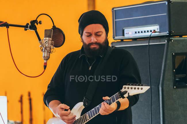 Erwachsener Mann im Musikstudio spielt Gitarre und singt in Mikrofon — Stockfoto