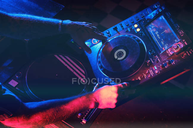 Hands of anonymous dj man playing in a club with lights — Stock Photo