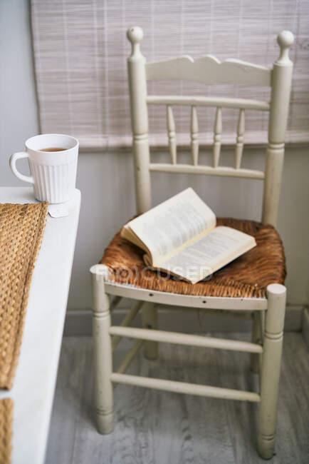 Утішне крісло з розгорнутою книгою розміщене біля столу з чаєм свіжого чаю в затишній кімнаті. — стокове фото