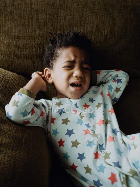 Carino ragazzo afroamericano in pigiama sdraiato sul comodo divano e iniziare a piangere a casa — Foto stock