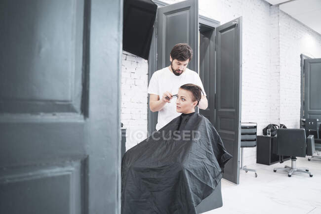 Hairdresser cuts woman's hair with scissors — Photo de stock