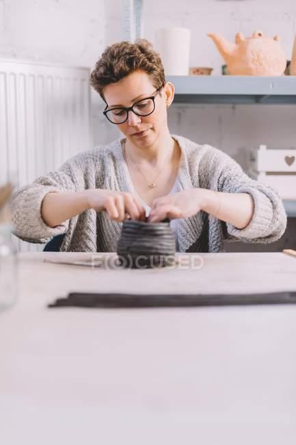 Взрослая женщина-гончар кладет мягкую глиняную полоску на вазу, сидя за столом в мастерской — стоковое фото