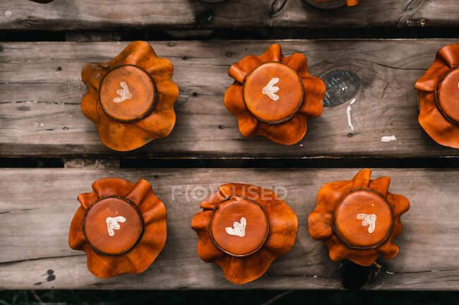 Set aus winzigen, mit schäbigen Lederdeckeln bedeckten Proviantgläsern, die auf einer alten Holzoberfläche in der Landschaft platziert wurden — Stockfoto